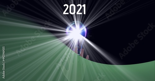 Composition of green copy space over year 2021, hand and lit lightbulb, on black