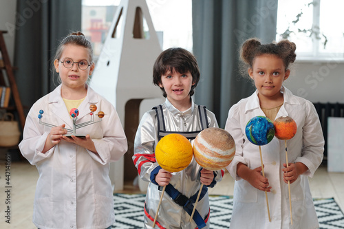 Foto Three adorable kids holding models of planets of solar system