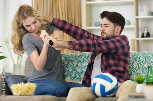 Fototapeta couple fighting over a remote