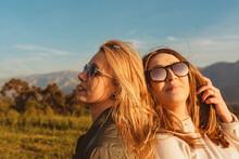 Stylish Women On Meadow In Mountains