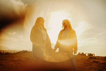 Crop Close Women Holding Hands In Sunset