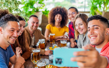 Diverse Group Of Friends Making A Selfie Celebrating Happy Hour With Beers And Food In A Bar Restaurant. Multiethnic People Having Fun In A Party Together Smiling At The Camera. Self Portrait Concept