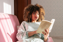 Thoughtful Black Woman Reading Book At Home