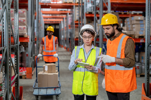 Canvastavla Two warehouse employees with tablet discussing working points