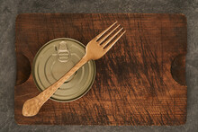 Cutting Board With Sealed Can And Fork On Wooden Table