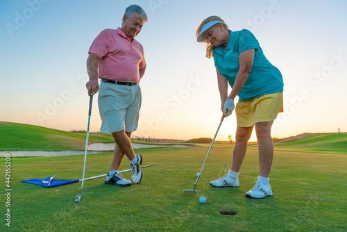 Billede på lærred Active senior couple playing golf at sunset at the putting green.