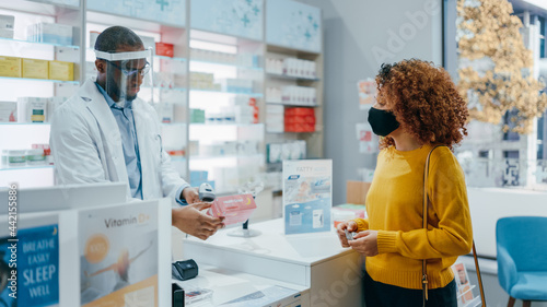 Obraz na plátne Pharmacy Drugstore Checkout Counter: Professional Black Pharmacist Wearing Face Shield Sells Medicine to Young Female Customer, who is wearing Face Mask, Use Contactless Payment