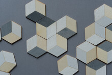 3d Wooden Cubes (hexagons) Hand Painted In White And Various Shades Of Gray Acrylic Paint, Loosely Arranged On A Medium Gray Paper Background, And Photographed From Above In A Flat Lay Style With Ambi