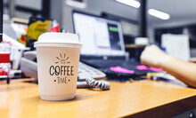 Paper Cup Of Coffee On Table In Office With Soft-focus And Over Light In The Background