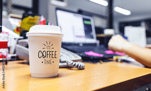 Photo paper cup of coffee on table in office with soft-focus and over light in the bac