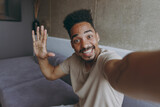 Close up fun happy smiling young african american man in beige casual t-shirt sit on grey sofa indoors apartment doing selfie shot on mobile phone waving hand say hello, rest on weekends stay at home