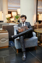 Vertical Full Length Portrait Of Successful Middle-Eastern Businessman Reading Documents While Sitting In Armchair At Hotel Lobby