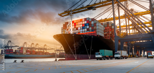 Fototapeta crane loading cargo container from truck to container ship in the international