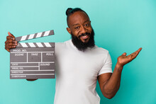 African American Man Holding Clapperboard Isolated On Blue Background Showing A Copy Space On A Palm And Holding Another Hand On Waist.