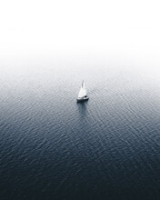 Vertical Shot Of A Sailboat Isolated In The Calm Ocean