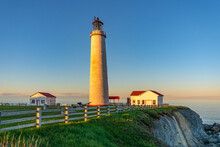 View At Sunset On The Atlantic Ocean, The Cliffs And The Cap Des Rosiers Lighthouse, The Highest Lighthouse In Canada, Located Near Forillon National Park In Quebec