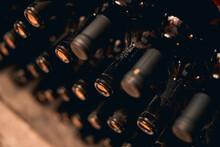 Dusty Bottles Of Red Wine In Wine Cellar