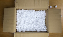 A Cardboard Box With Packing Foam Top View, Delivery Box For Fragile Product On Wooden Table