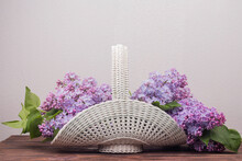 Beautiful White Vintage Wicker Basket On A Wooden Table. Lilac Flowers In A Retro Basket