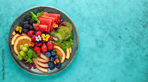 Delicious healthy salad of fresh fruits, berries and edible flowers on plate. Clean eating. Top view.