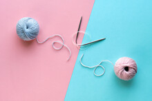Wool Yarn Balls And Knitting Needles With String On Split Pink And Mint Blue Paper Background. Creative Minimal Simple Flat Lay, Top View, Craft Concept Picture.