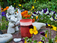 Blooming Flower Garden With An Angel Statue