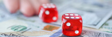 Womans Hand Throwing Red Dice On Dollar Bills Closeup