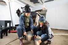 Female Farmers With Buckets Milking Goat In Barn