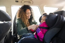 Mother Fastening Daughter Into Car Seat In Back Seat