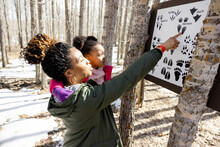 Mother And Daughter Looking At Animal Paw Prints On Sign