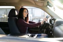 Cheerful Woman Sitting Behind Wheel Of Vehicle