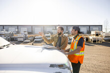 Colleagues Discussing Work Beside Truck In Industrial Yard
