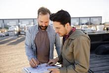 Customers Looking At Sketch Plan In Industrial Yard