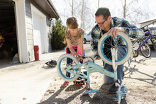 Father And Daughter Lubricating Bicycle Chain In Yard