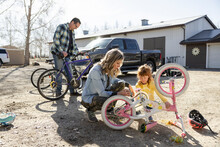 Mother And Daughter Greasing Bicycle Chain In Yard