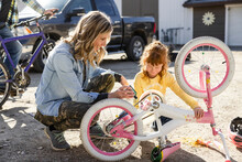Mother And Daughter Lubricating Bicycle Chain In Yard