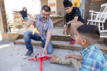 Father And Sons Assembling Toy Rocket On Base