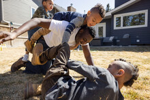 Father And Children Playing Piggyback On Backyard Lawn