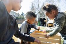 Siblings Looking At Seed Sachet In Wooden Crate