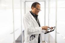 Male Doctor In Lab Coat Using Digital Tablet In Clinic Corridor