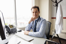 Portrait Confident Handsome Male Doctor At Desk In Clinic Office