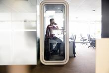 Male Nurse Talking On Smart Phone In Clinic Office Pod