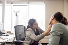 Doctor Examining Neck Of Patient In Clinic Office