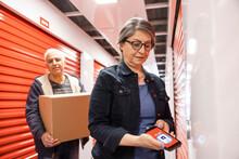 Senior Woman Unlocking Storage Facility Locker With Smart Phone App
