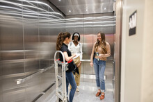 Young Women With Hand Truck In Storage Facility Elevator
