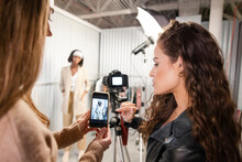 Female Fashion Influencers Photographing Model In Storage Facility