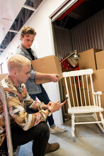 Young Men With Smart Phone Moving Belongings In Storage Facility