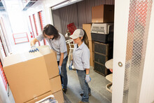 Movers With Boxes At Storage Facility Locker