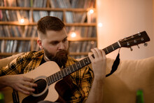 Young Handsome Man Playing Guitar At Home