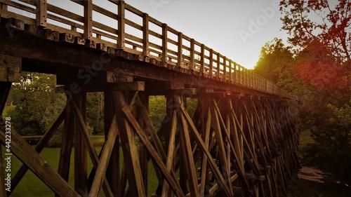 Fotografie, Obraz Side view of a wooden trestle narrow footbridge at sunset